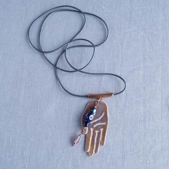 MYSTIC HAND long necklace, palmistry, hamsa, evil eye, sepia glaze, white porcelain, grey leather thong, rose gold zamak bail, beads, cerami