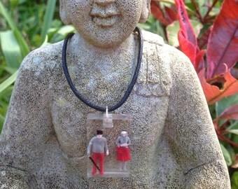 Handmade resin pendant with minature couple.