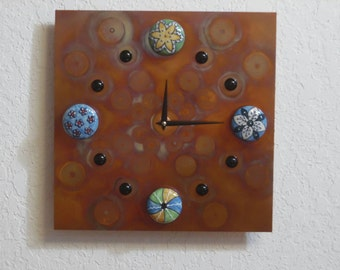 Decorative torched copper wall clock with ceramic cabinet knobs.