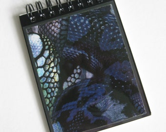 "Alexander McQueen A7 (11x18cm) spiral-bound notebook made with ""Black Snake' print paper."