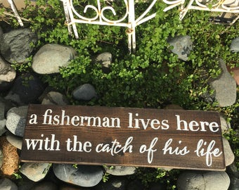 """a fisherman lives here with the catch of his life 5.5""""x18"""" hanging wall decor- mancave- husband love"""