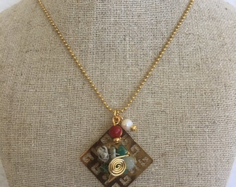 Necklace with gold-filled pendant and various stones.