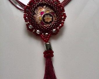 Pendant in a burgundy aura with silver sprinkles ... Handmade Beaded pendant