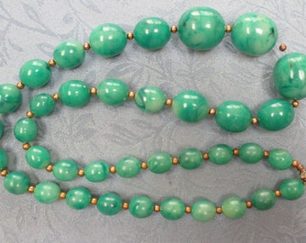 "A vtg.plastic beaded chunky necklace in green marbleized beads with gold spacers--26"" end to end"