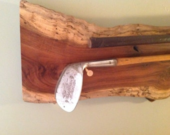Antique golf clubs mounted on walnut
