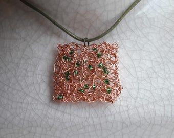 Square copper pendant with green beading. Crocheted in wire and hangs on green leather thong.