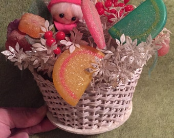 Vintage 1950s Christmas decoration. Floral arrangement with cute elf and faux candy and plants in white wicker basket. White and pastel.