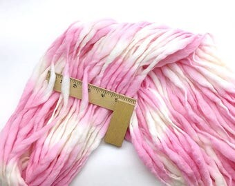 55 yards, 3.5 ounces/ 100 grams handspun thick and thin yarn, spun super bulky in hand dyed pink and cream merino wool