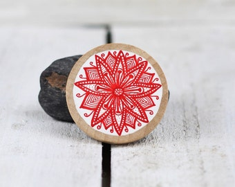 round circular wooden brooch with hand drawn red flower design on white
