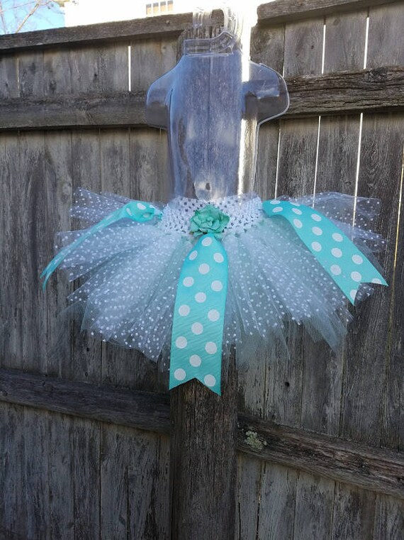 White and aqua tutu with grosgrain ribbon accents.  One size fits most toddler girls