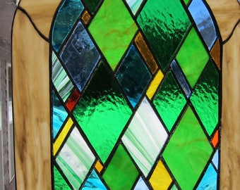 Emerald city stained glass window hanging suncatcher in various textures of green glass with  amber, red, yellow/orange and blue accents.