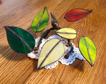 Group of stained glass leaves on brass branch stand with brass bird