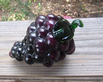 bunch of purple glass grapes, green leaf and stem