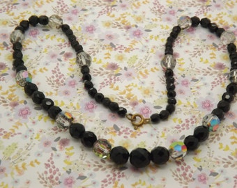 A fine period crystal bead vintage jewelry necklace made of sparkly faceted black and smoky rainbow crystal beads