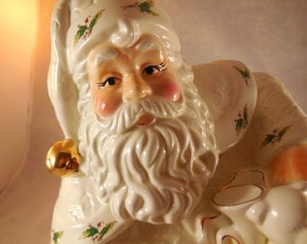 Santa Clause cookie jar, santa with his bag of toys in white and gold ceramic.