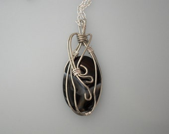 Wire wrapped pendant. Black marbled with gray. Wrapped with silver plated copper. Silver chain.