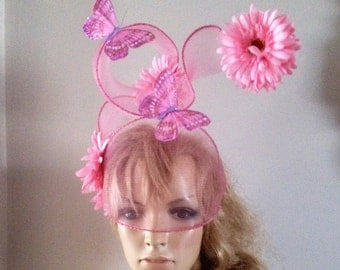 pink veiled headpiece adorned with sculptured spiral,flower and glitter encrusted feather butterflies