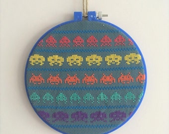 Space Invaders Cross stitch in a blue 6 inch embroidery hoop on blue aida fabric