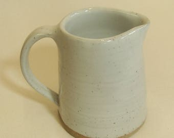 Stoneware jug with speckled white glaze.