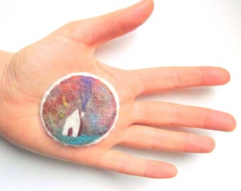 Felted pin, wearable art piece with a cottage and multicoloured sky.