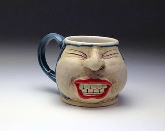 Ceramic face mug handmade blue coffee cup hand built big teeth nose smile expressive funny ironic funky large pottery by Molly Morning-glory