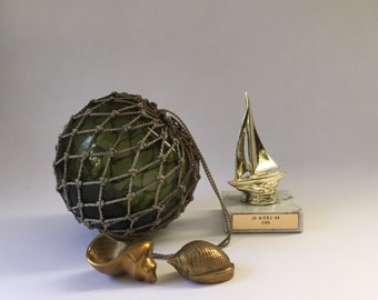 vintage green glass float in a rope net, old ocean working nautical float, rustic modern beach house lake sailing fishing garden décor