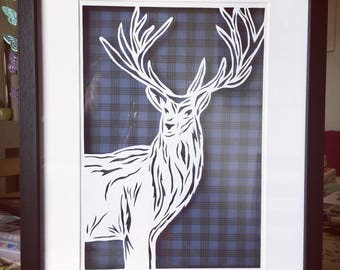 Paper cut stag framed over blue & black tartan