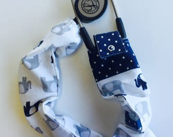 Stethoscope cover featuring a white material with grey elephants and polka dots
