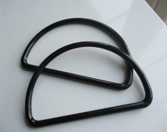 A pair of plastic black handbag handles.
