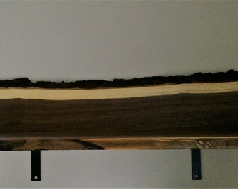 Live edge walnut shelf with bark on one edge only.