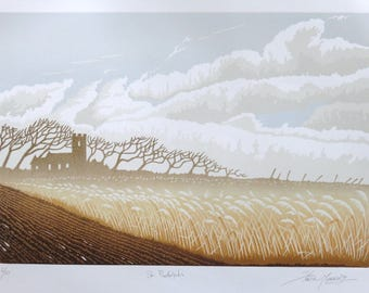 Lino cut print of St Botolph's church Lincolnshire with reed beed, silhouette trees, rutted track and big, cloudy sky.