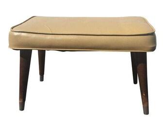 Mid Century Modern Vinyl Foot Stool.  Classic 1960s madmen style chair foot rest. Retro upholstered in cream/yellow/tan vinyl ottoman