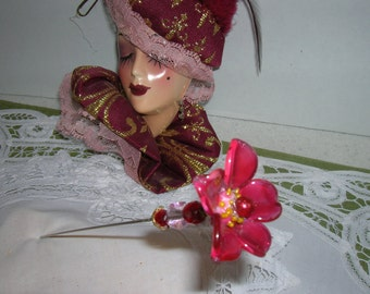 A mauve colored lampwork glass flower is in bloom at the top of this antique hat pin