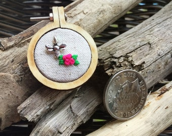 Tiny embroidery hoop brooch. Flowers and bee on linen.