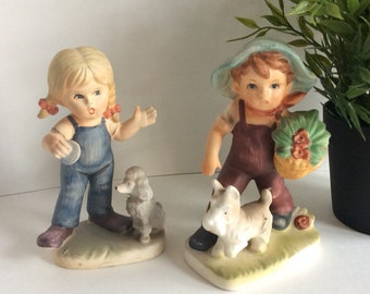 Mid century Our Children figurines. Little boy with Scottie dog, and Little girl with poodle. Porcelain figures made by Norton.