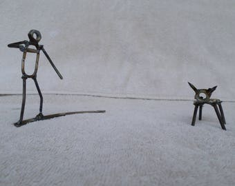 welded metal dog and person playing frisbee sculpture
