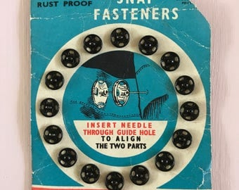 Newey black snap fasteners or poppers or press studs from the 1970's.  Vintage retro sewing eqipment.