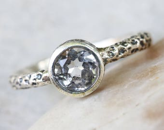 Round faceted white topaz ring in brass bezel setting with sterling silver oxidized hard texture band