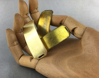 Three curved brass pieces with rectangular holes