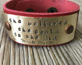 An red leather cuff with hand stamped and riveted brass plate she thought she could so she did