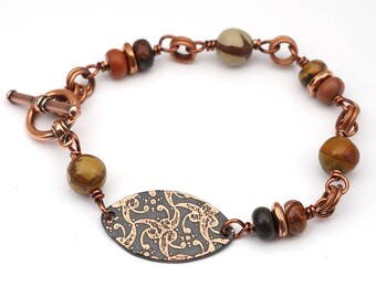 Copper floral design bracelet, warm earthtones, multicolor red creek jasper beads, etched jewelry, 7 inches long