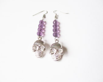 Purple skull earrings: Chic, shiny purple beaded earrings hung with silver tone skull charms, inlaid with white rhinestone eyes, pierced