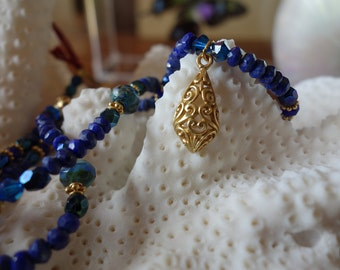 Gold scroll pendant and blue lapis lazuli beaded necklace