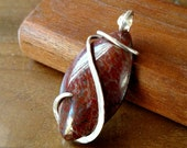 Red dinosaur bone and sterling silver wire wrapped pendant. Simple design.