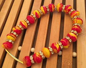 7.5 inch gold and orange and yellow with clear rhinestones beaded stretch bracelet.