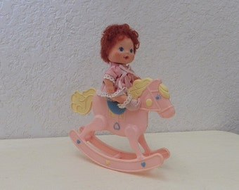 Strawberry Shortcake  BERRY BABY Strawberry Doll, 1984 riding a Heart Family Rocking Horse. Found other booty and cap.