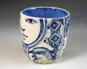 Blue and white story cup porcelain, one of a kind with faces, bird and I think a dragon