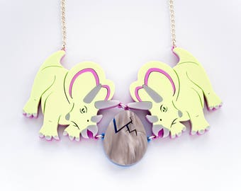 Triceratops watching a hatching egg dinosaur necklace. Laser cut pastel acrylic prehistoric animal bib. Perspex statement necklace. Dino egg