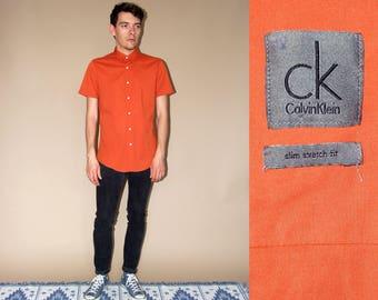 90's vintage men's Calvin Klein orange slim stretch fit shirt