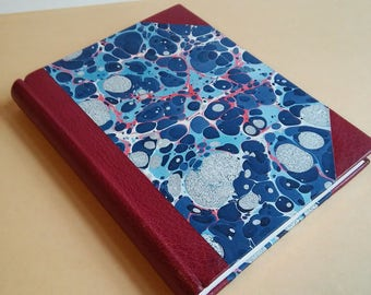 Leather bound journal with blue stone-pattern marbled cover.